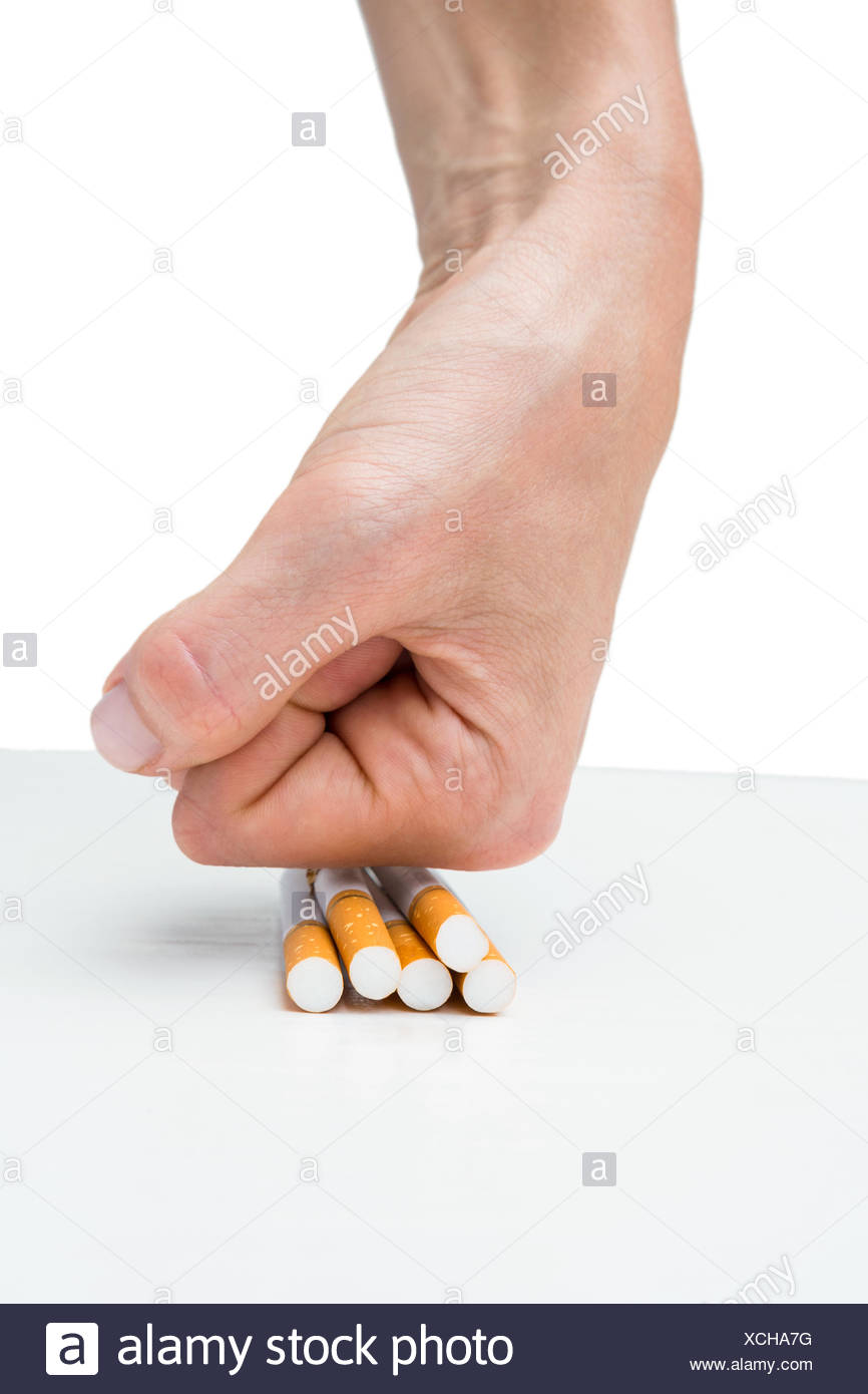 Hand squashing batch of cigarettes - Stock Image