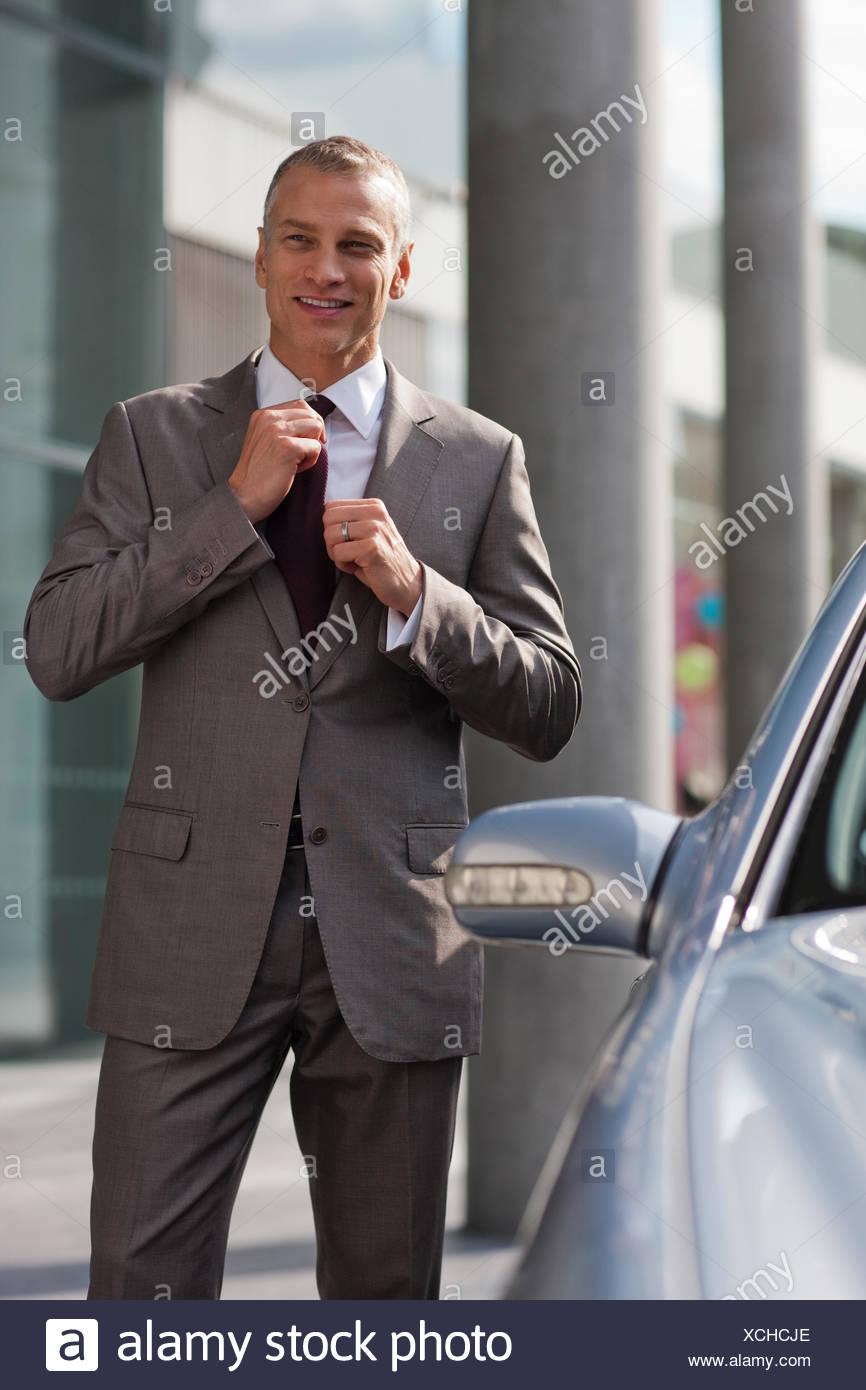 Businessman adjusting necktie outdoors - Stock Image