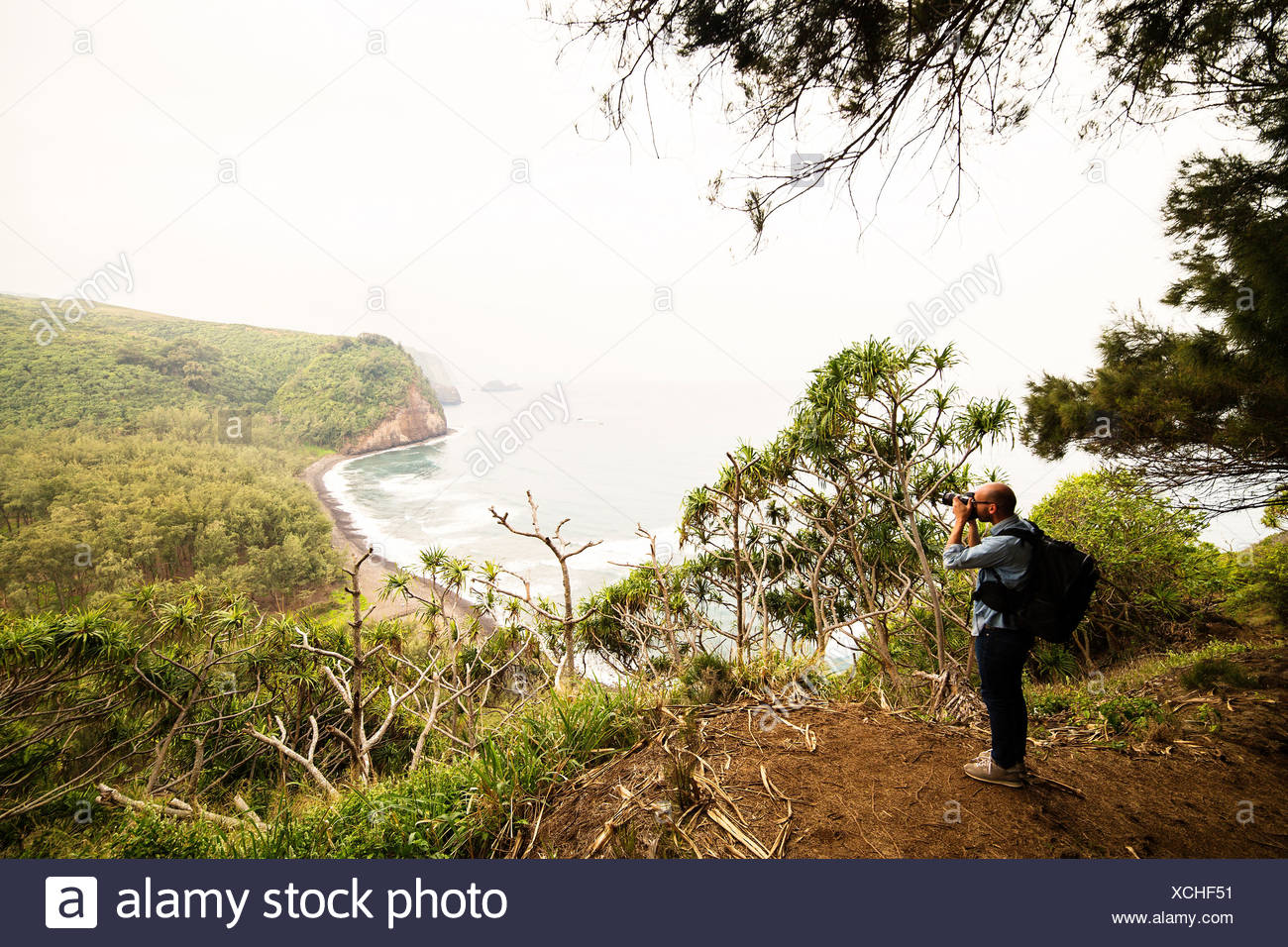 Mid adult man photographing coastline - Stock Image