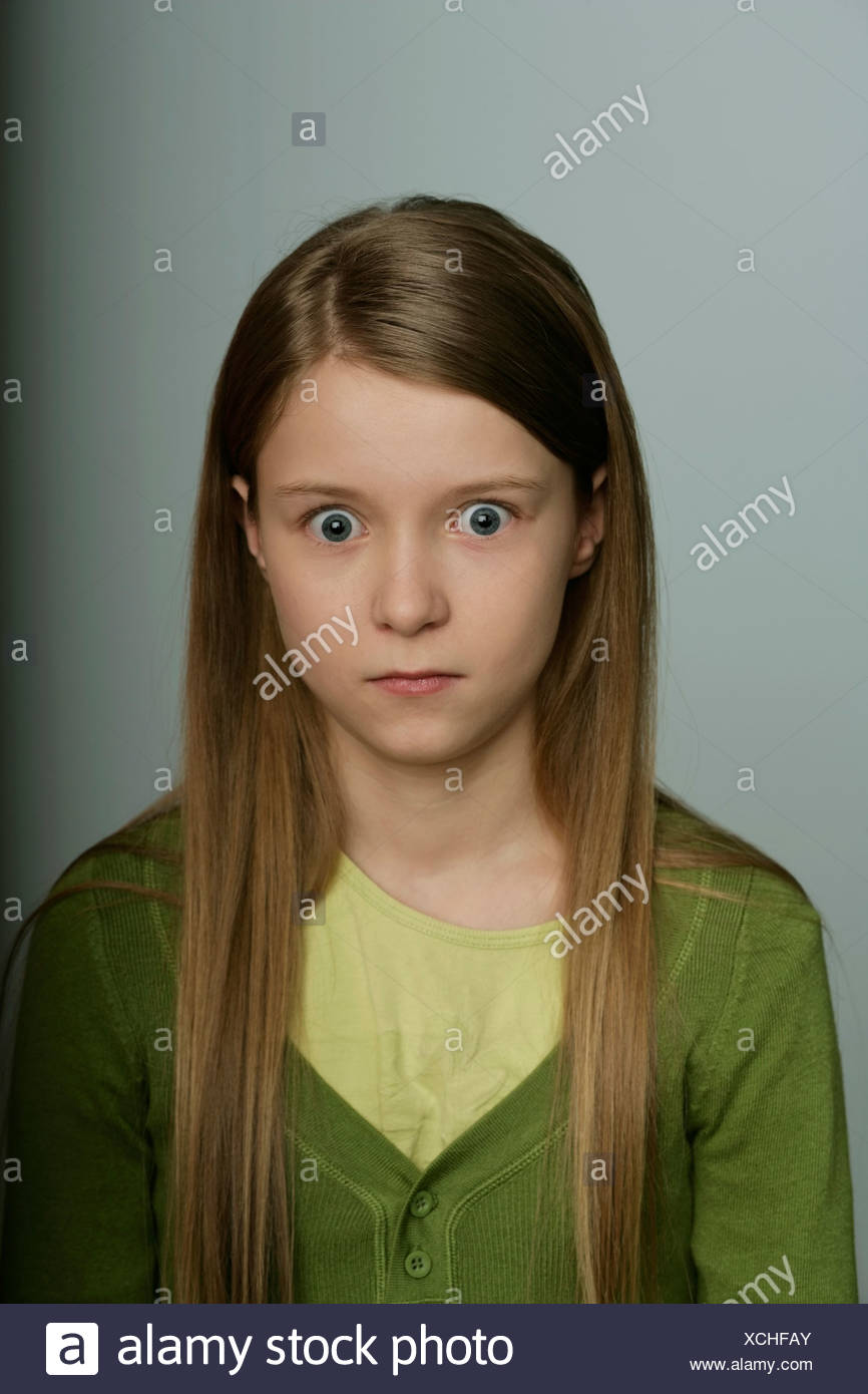 Scared girl looking at camera - Stock Image