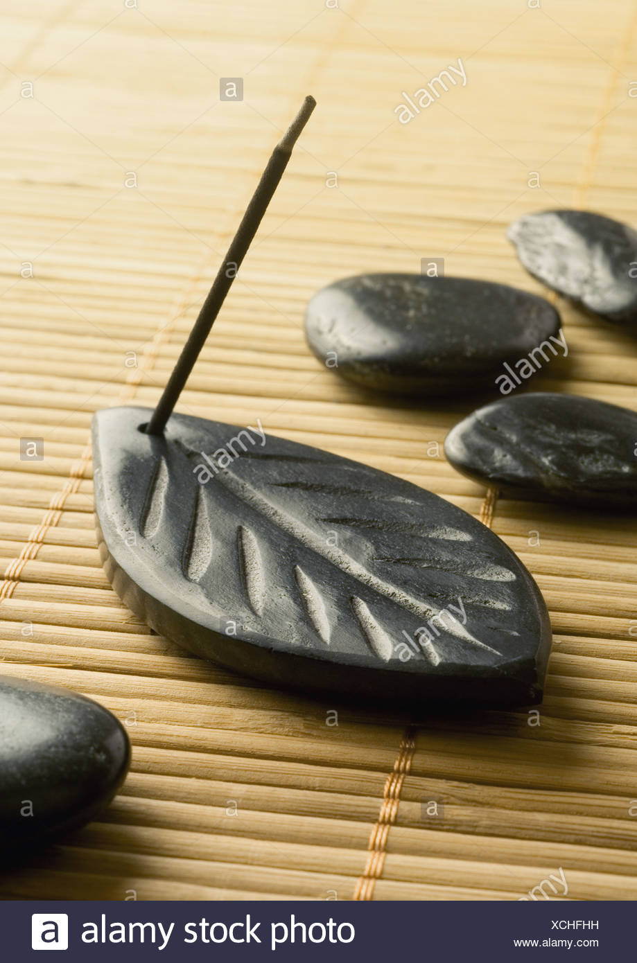 Stick of incense burning in incense holder and smooth black stones - Stock Image