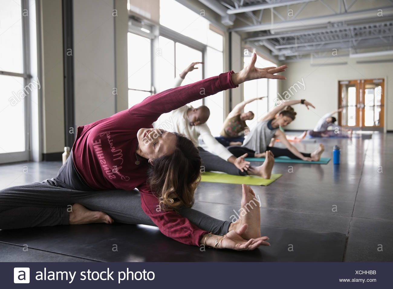 Woman practicing wide legged seated side bend in yoga class studio Stock Photo
