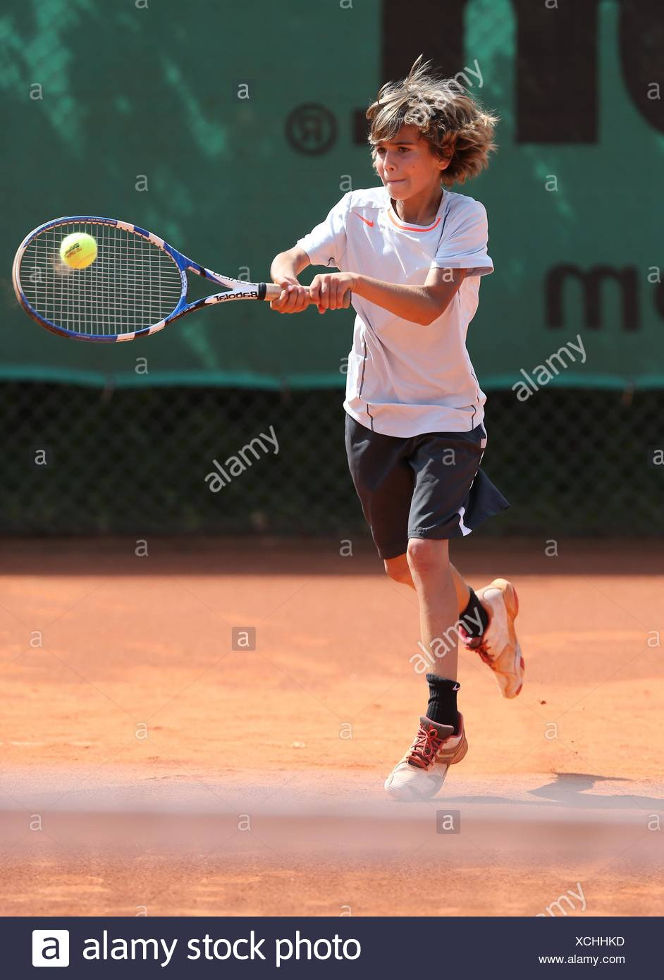 Boy, 10, playing tennis, hitting with a two-handed backhand, Munich, Upper Bavaria, Bavaria, Germany - Stock Image