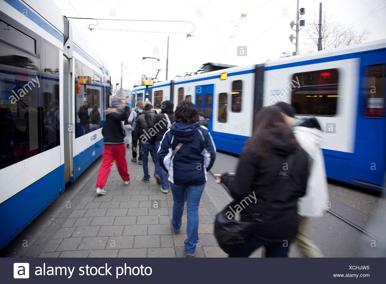 People walking between two streetcars. Amsterdam, Holland - Stock Image