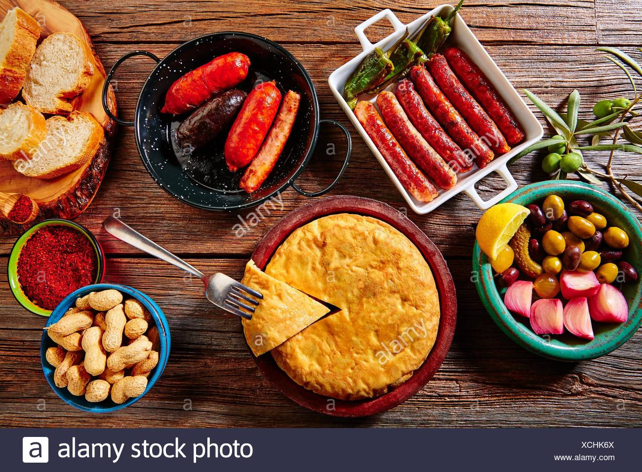 Tapas mix spanish potatoes omelette sausage olives bread and paprika. - Stock Image