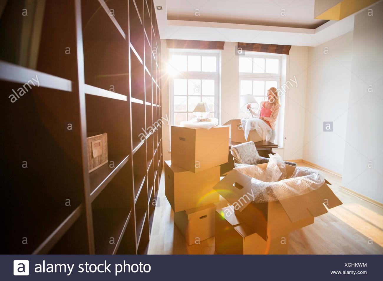 Woman unpacking lamp from moving box at new house - Stock Image