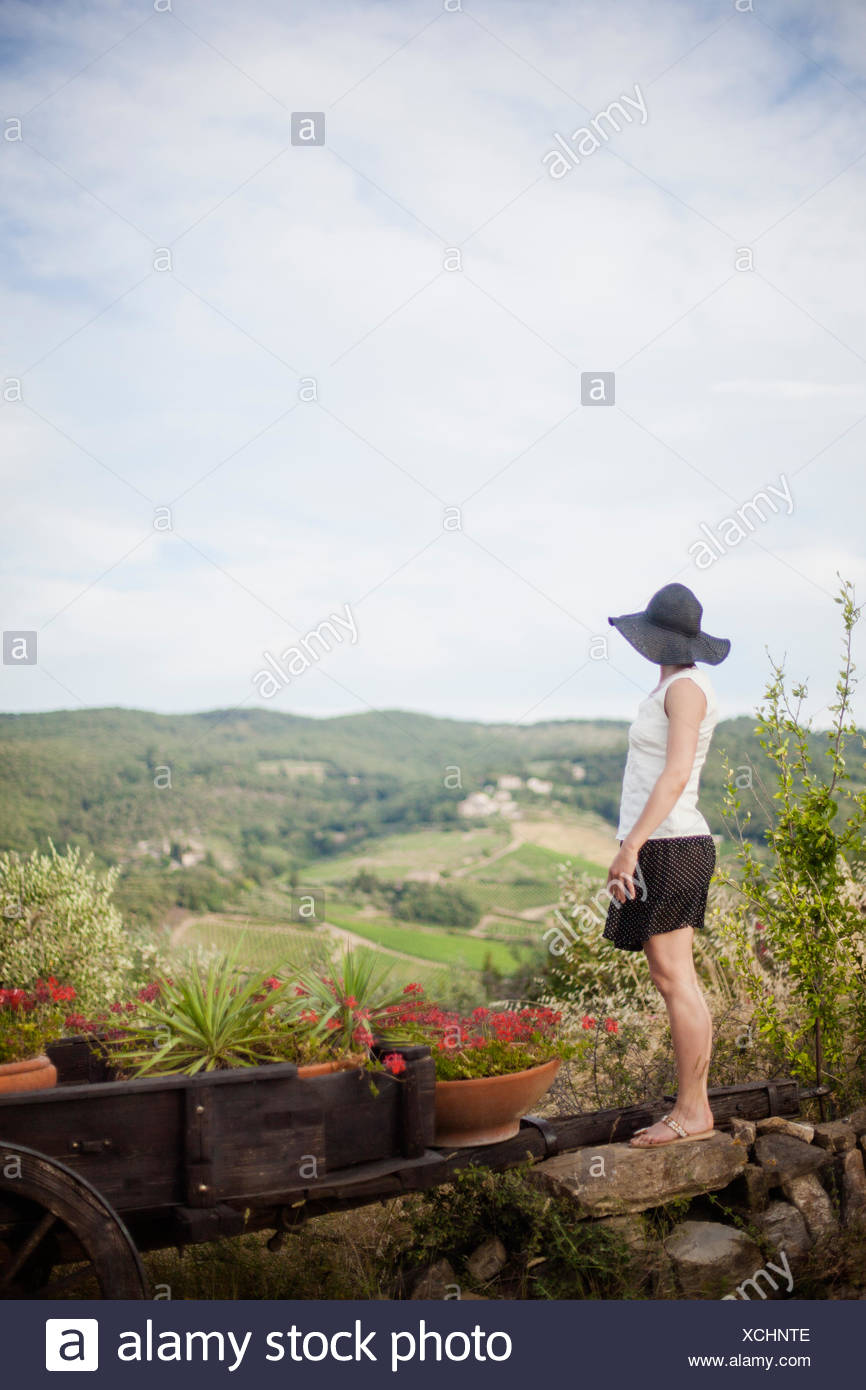 Italy, Tuscany, Woman in black hat looking at view - Stock Image