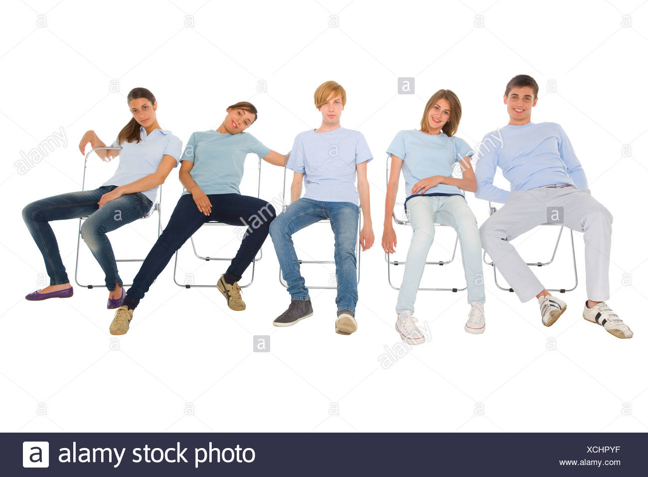 teenagers sitting on chairs - Stock Image