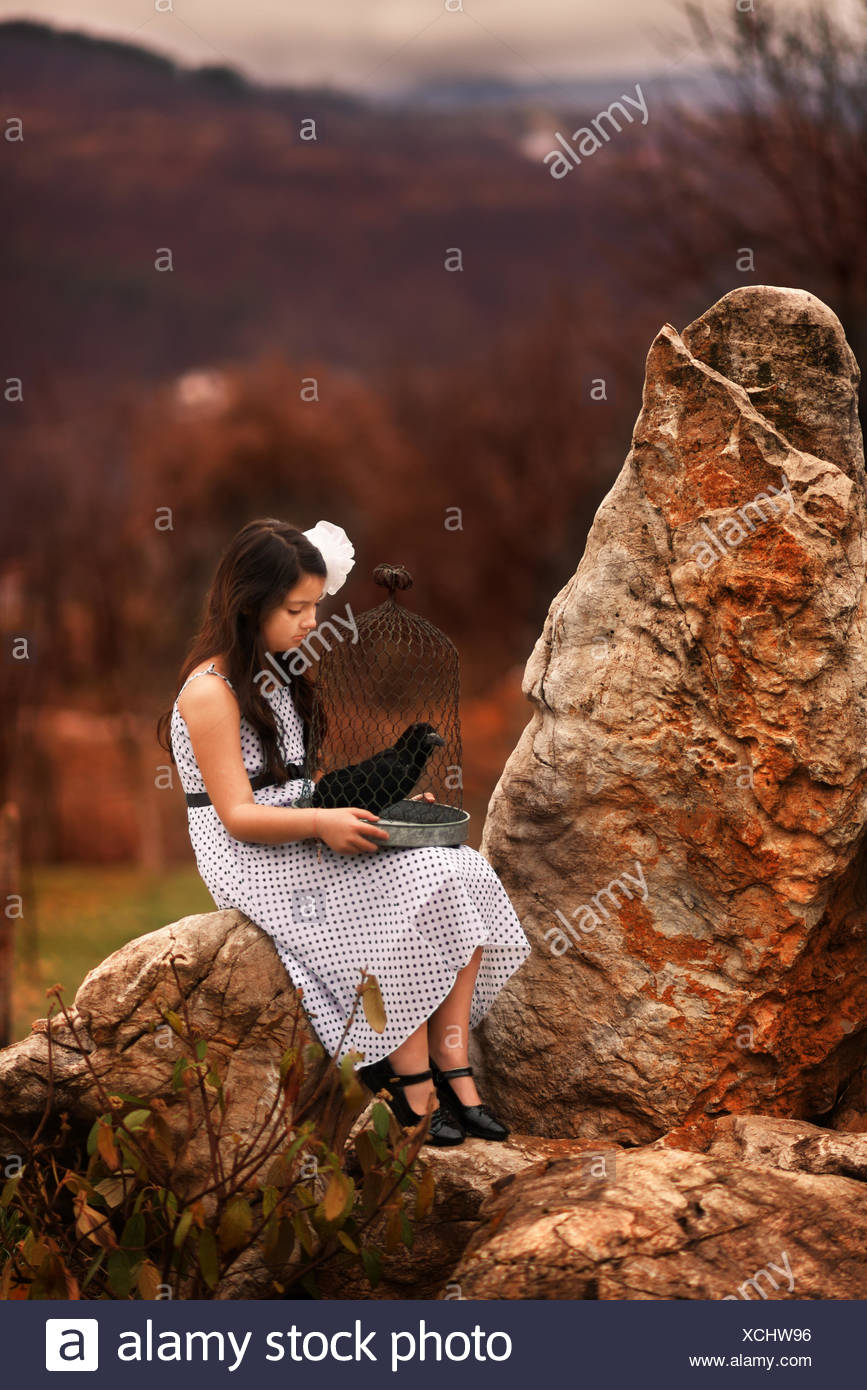 Girl sitting on rocks holding a bird cage with a stuffed black bird - Stock Image