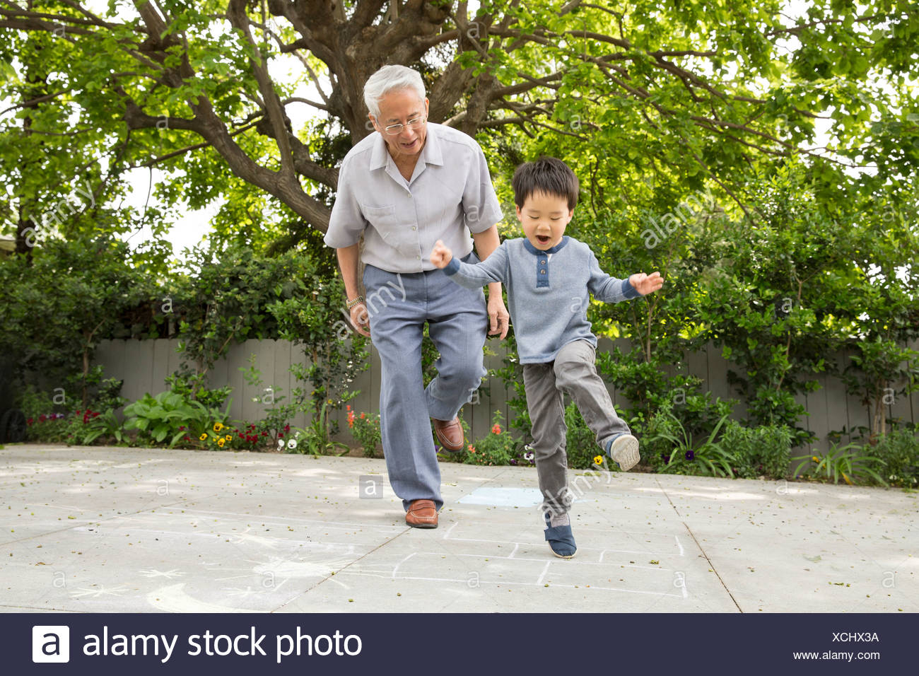 Grandfather playing hopscotch with grandson - Stock Image