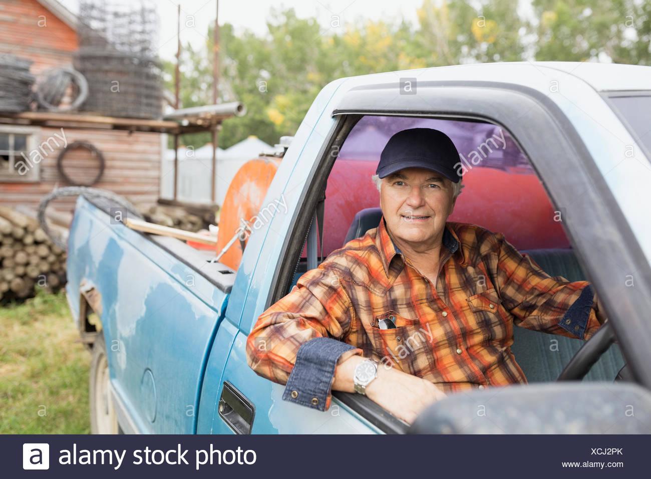 Portrait of confident farmer inside truck - Stock Image
