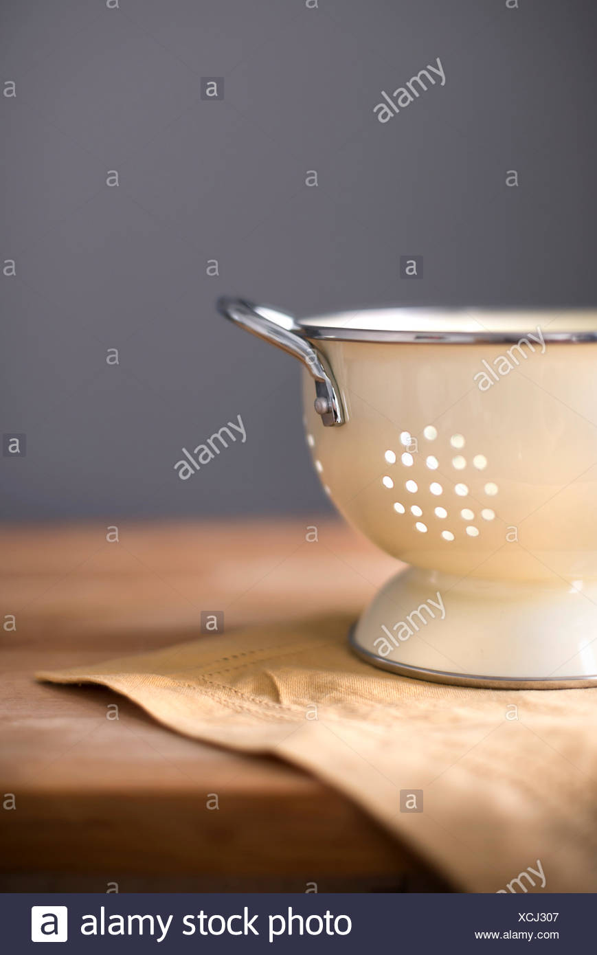 Small cream colored strainer on butcher block counter with a mustard linen. - Stock Image