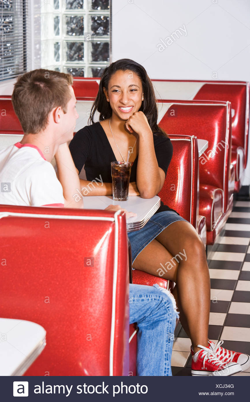 Teenage interracial couple on a date in a diner Stock Photo