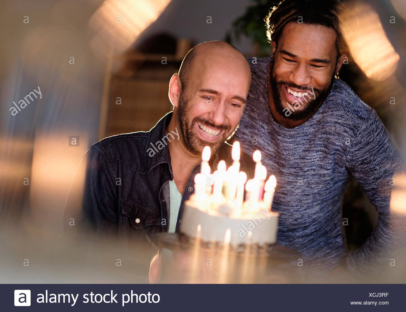 Smiley homosexual couple looking at birthday cake - Stock Image
