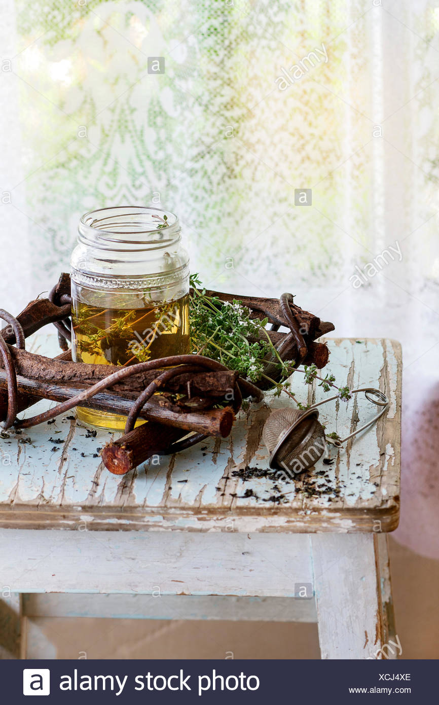 Glass jar of hot herbal tea with bunch of fresh thyme, served with vintage tea-strainer on old wooden stool with window at backg - Stock Image