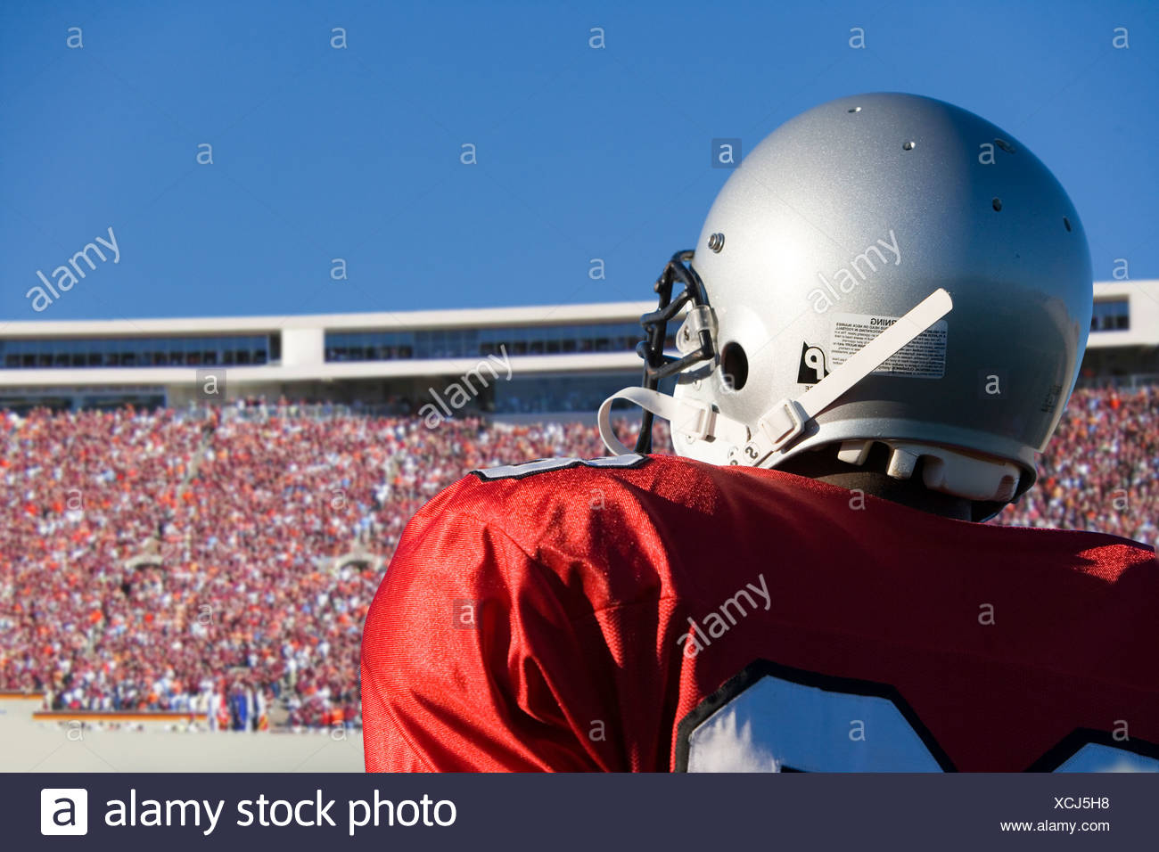Football player looking at crowd in stadium - Stock Image