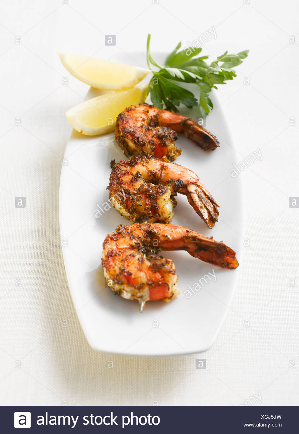 Grilled shrimps, parsley and lemon slices on platter, elevated view - Stock Image