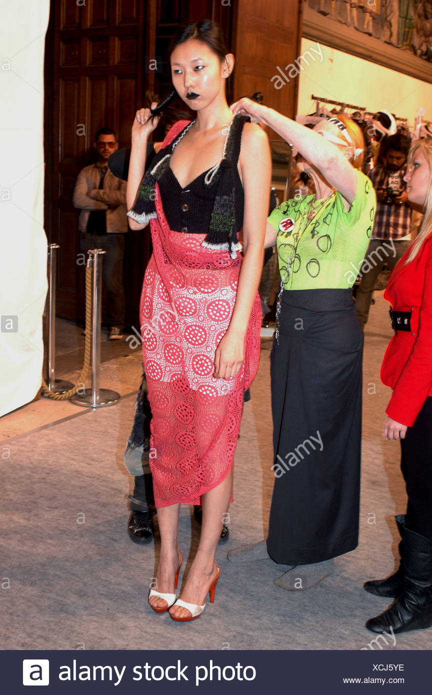 760d79bd68489 Vivienne Westwood Backstage Paris Ready to Wear Spring Summer Female  wearing cut away outfit and black lipstick being fitted by