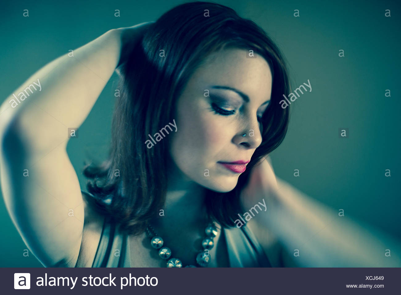 Portrait of mid adult woman, posing, hands behind head Stock Photo