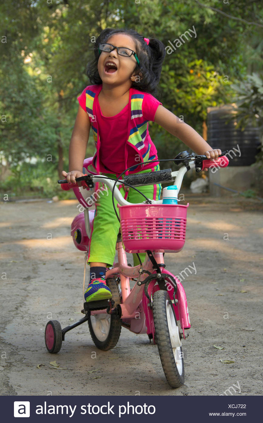 Little Indian girl with specs, dressed in pink on her bicycle - Stock Image