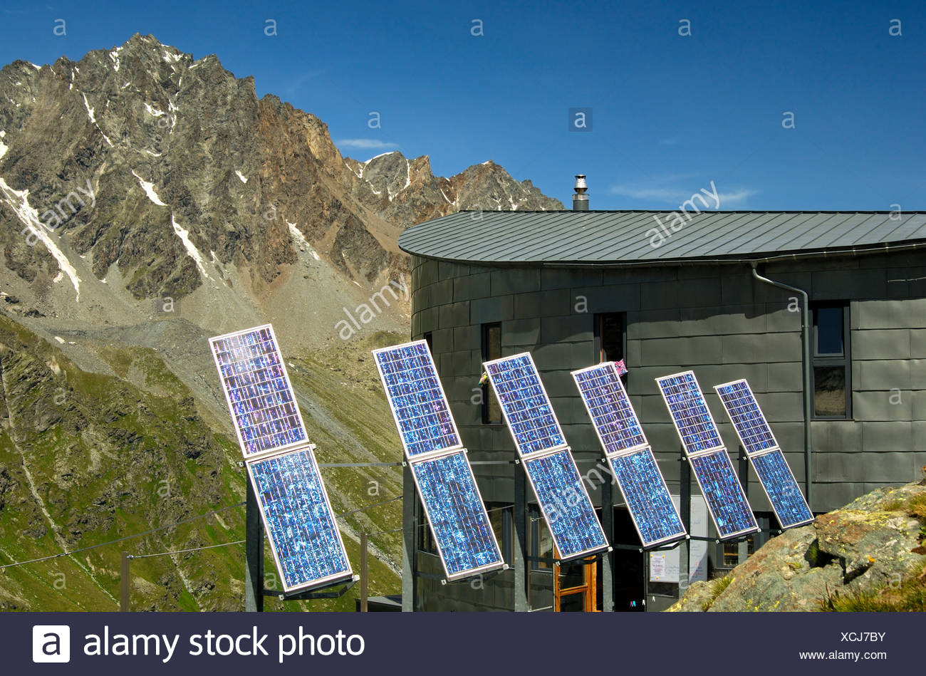 The futuristic Velan Hut, Cabane du Velan, of the Swiss Alpine Club, SAC, with its six solar panels in front of the summit of Stock Photo
