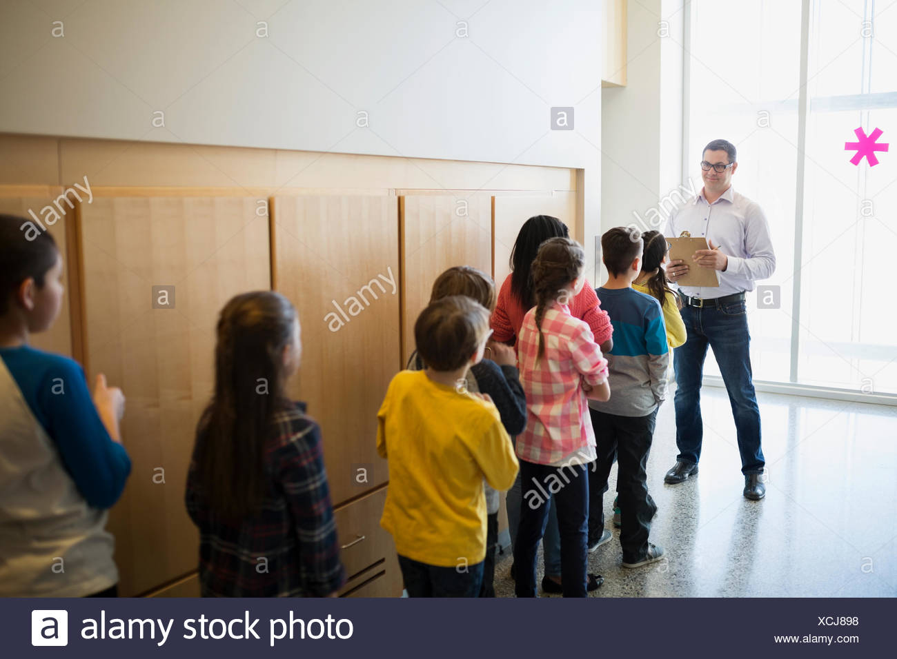 Teacher with clipboard and students lined up corridor - Stock Image
