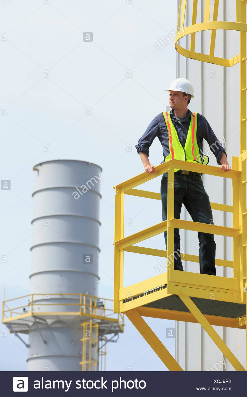 Industrial engineer on safety cage of fuel storage tank at
