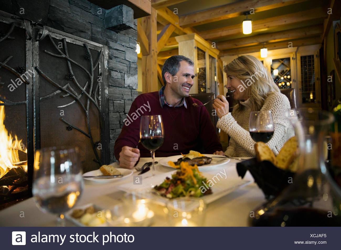 Couple enjoying fireside dinner at restaurant - Stock Image