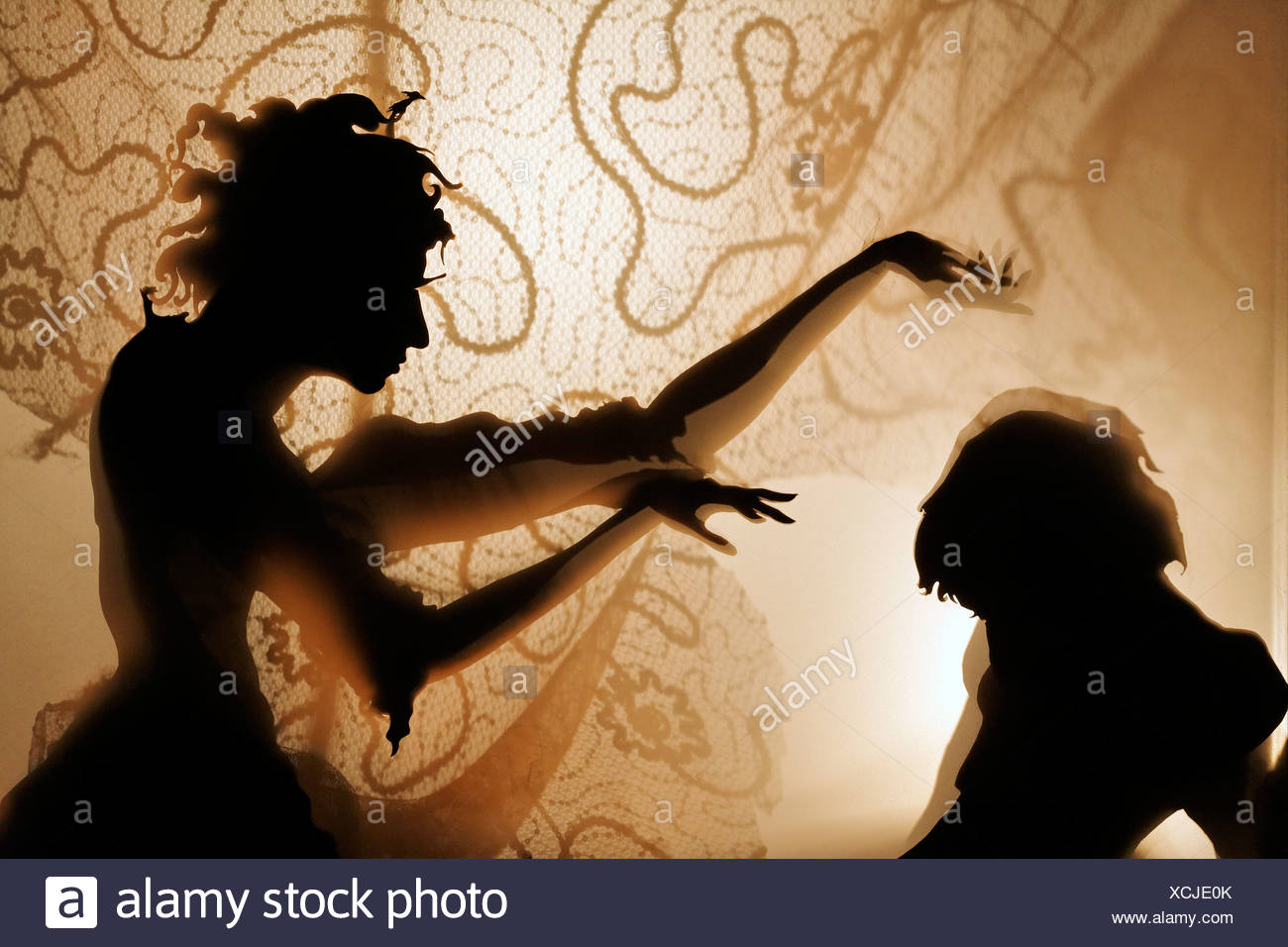 Woman bewitches a man, projection of silhouette figures on an illuminated curtain, shadow theater, tour Kunstakademie Art - Stock Image