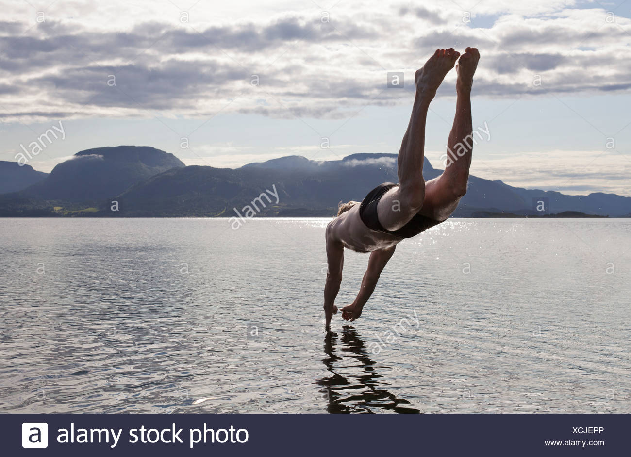 Man diving into water, Aure, Norway - Stock Image