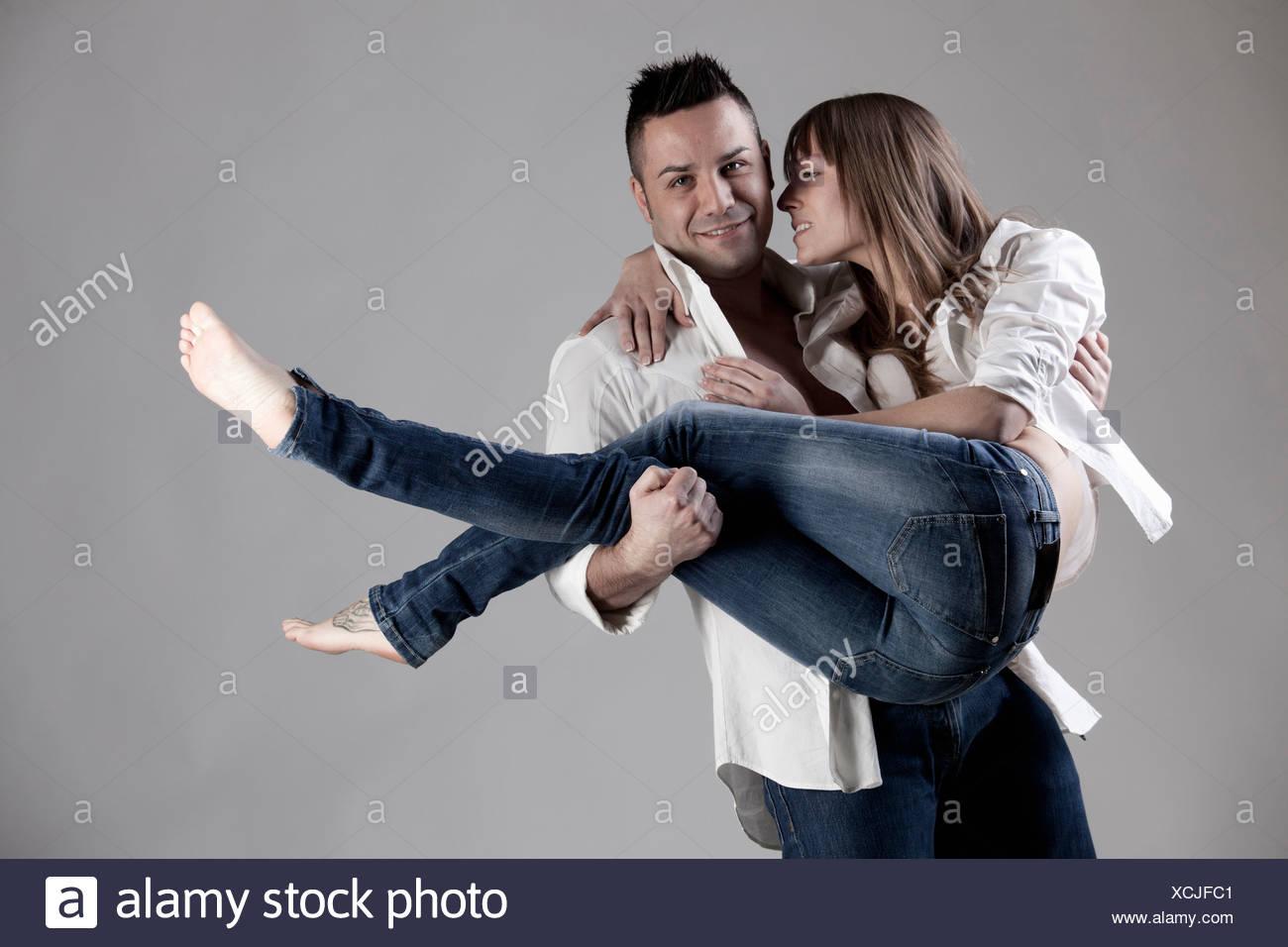 Smiling man carrying girlfriend - Stock Image