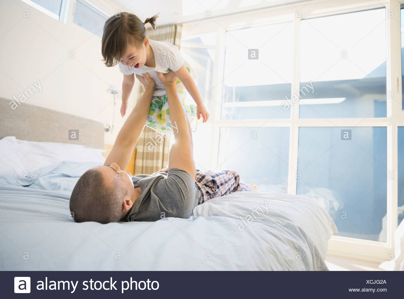 Father lifting daughter overhead on bed - Stock Image