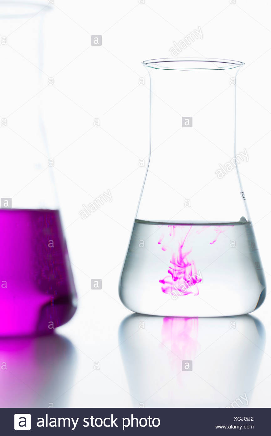 Volumetric flasks with colorless and pink on white background, close up - Stock Image