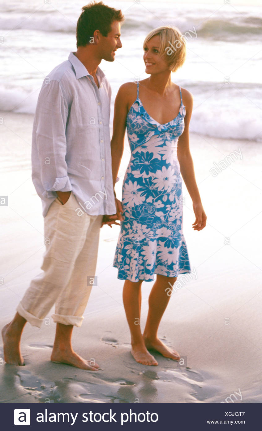 Female Short Blonde Hair Wearing Blue And White Floral Summer Dress Male Short Brown Hair Wearing Ivory White Rolled Up Linen Stock Photo Alamy