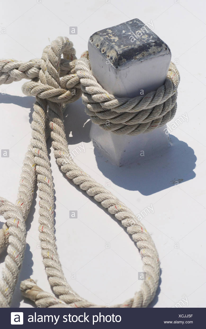 A rope tied to a cleat on a boat. - Stock Image