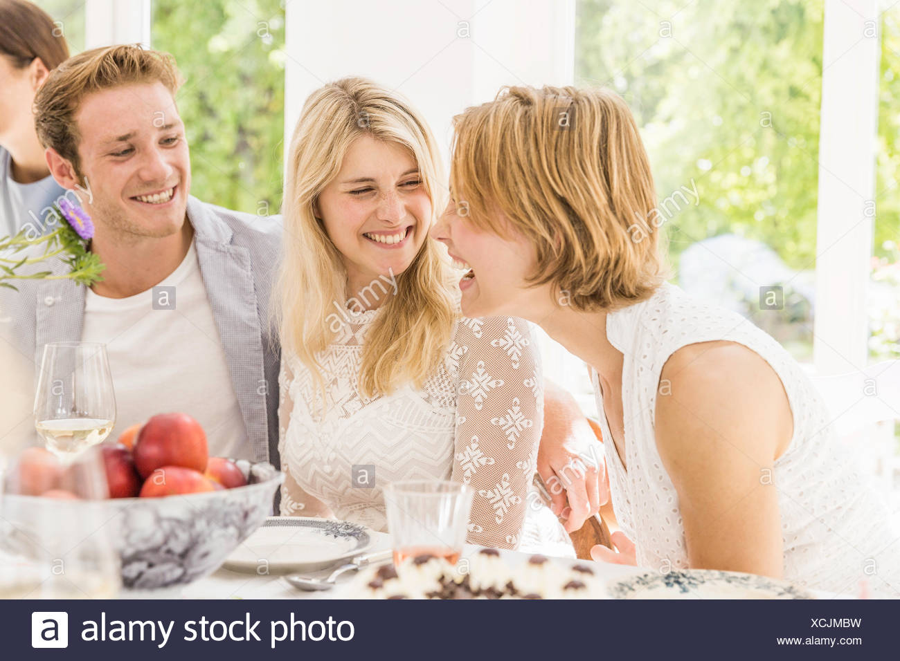 Family adults laughing and gossiping at birthday party - Stock Image