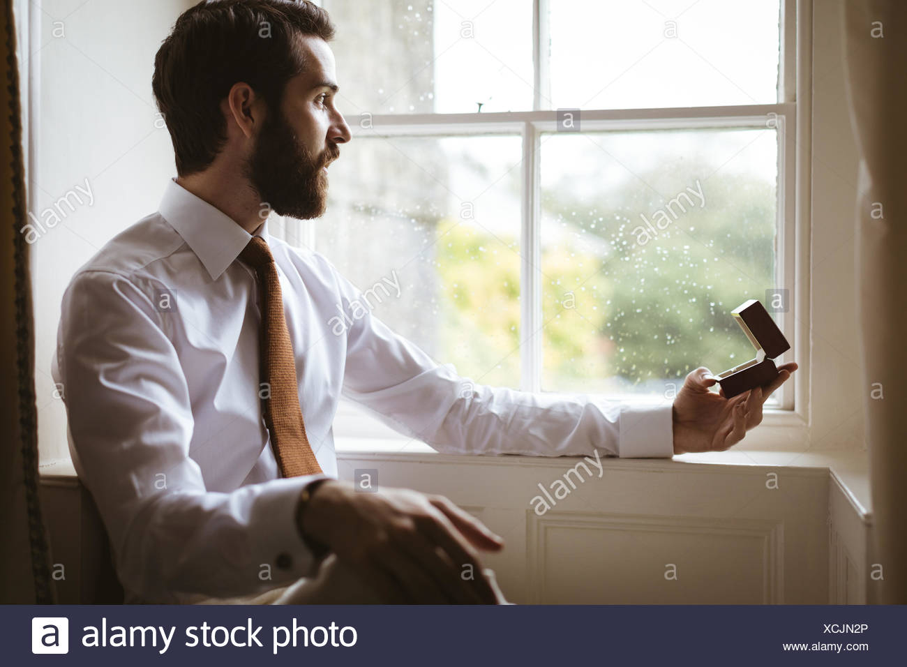 Groom sitting with ring box near window - Stock Image