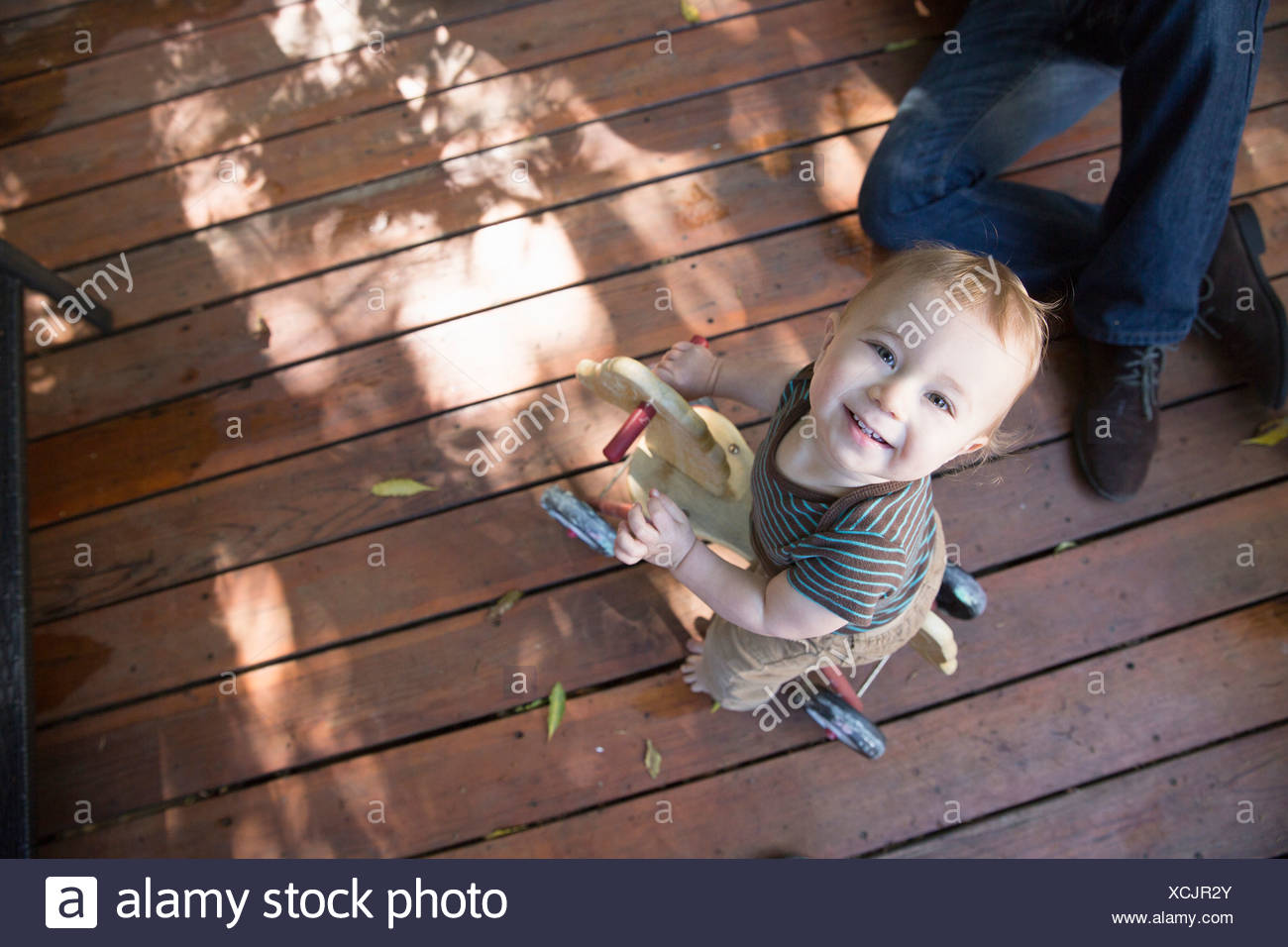 Baby riding on toy horse - Stock Image