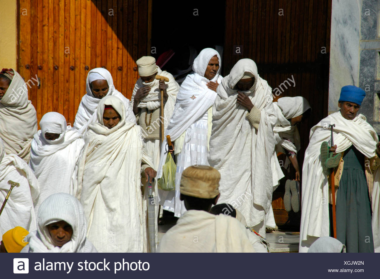 Believers of the Ethiopian Orthodox Church covered in white cloths in front of the new cathedral, Aksum, Ethiopia, Africa - Stock Image