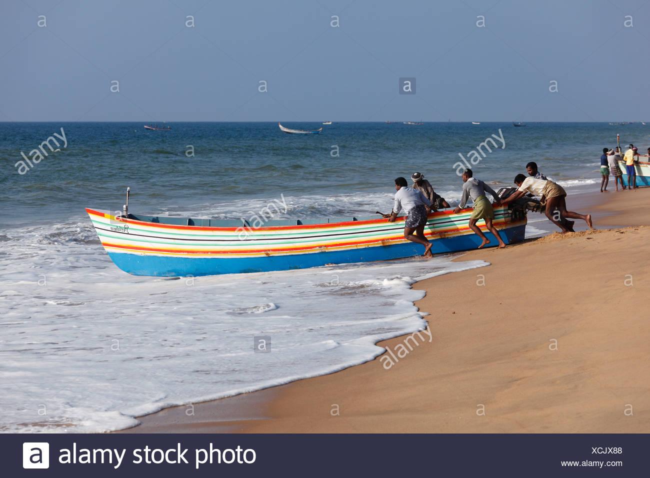 Fishermen pushing their fishing boat into the sea, Somatheeram Beach, Malabarian Coast, Malabar, Kerala state, India, Asia - Stock Image