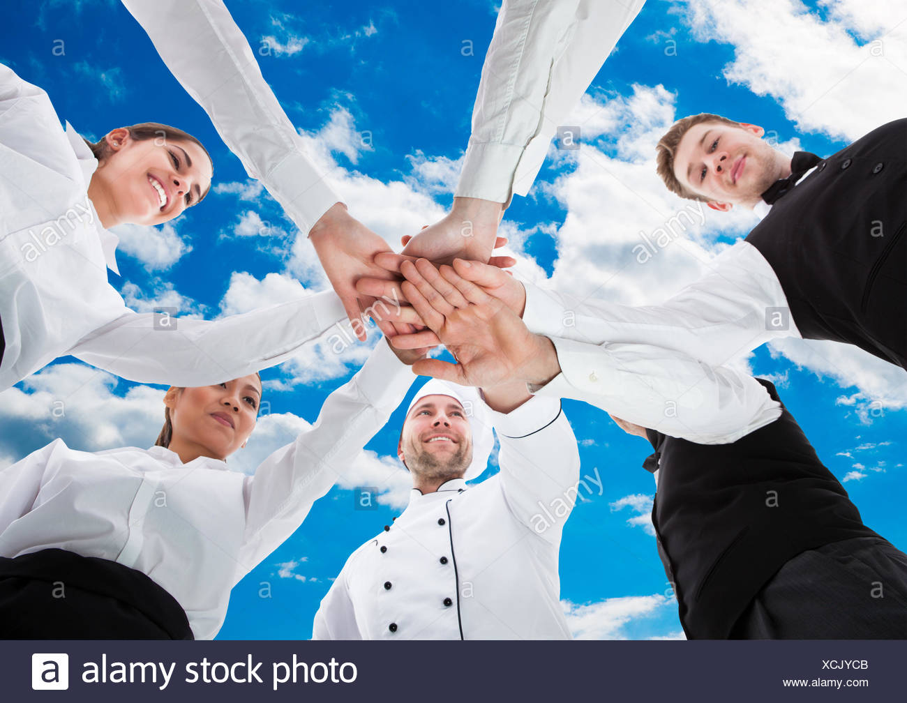 Waiters and waitresses stacking hands - Stock Image