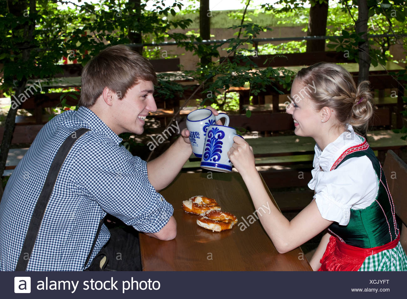 Young Couple In Dirndl And Lederhosen Clinking Their Beer Steins