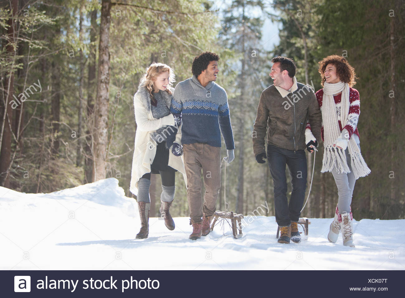 Four people with sled in snowy landscape - Stock Image