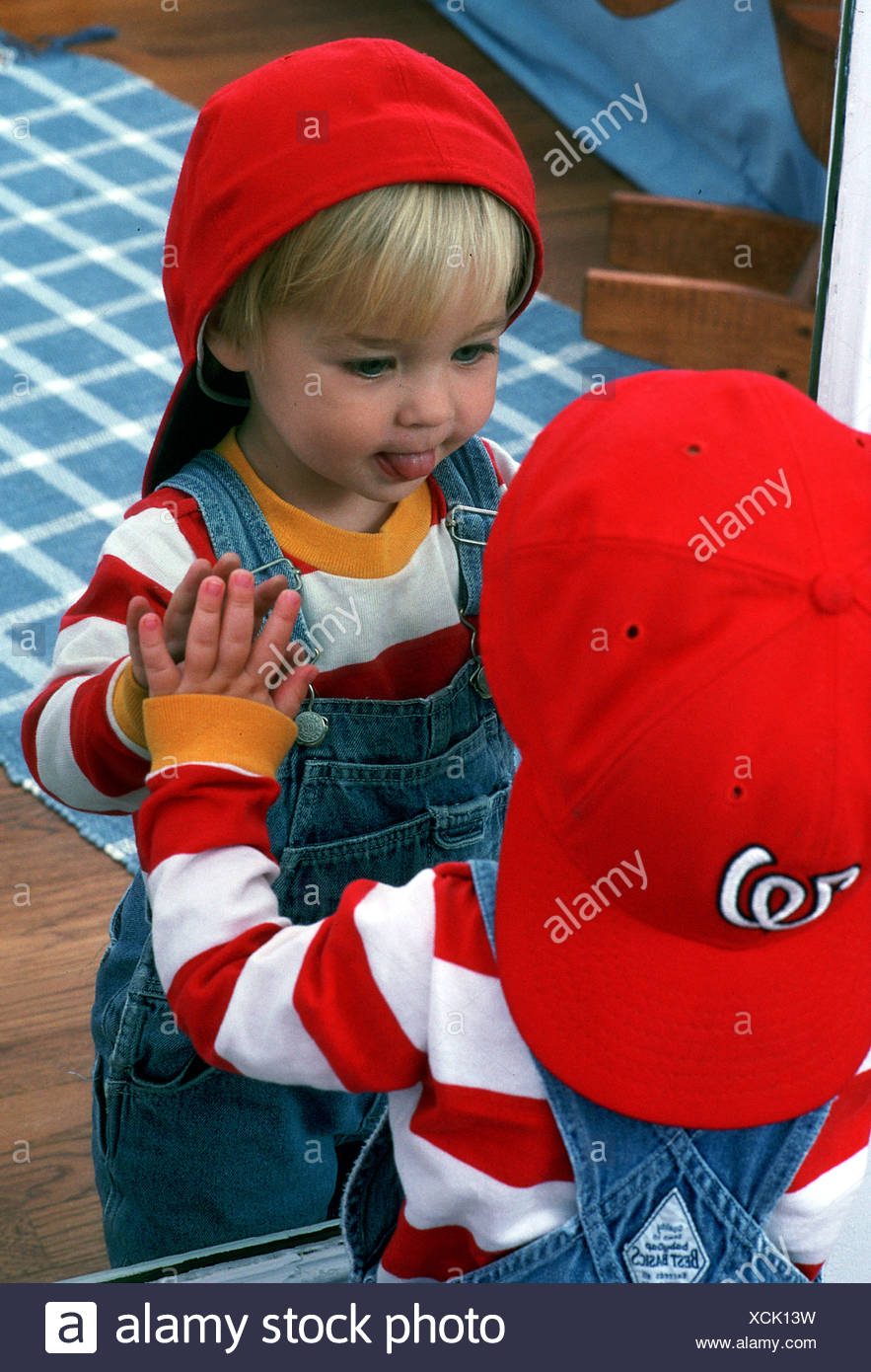 Toddler is fascinated playing with its image in a mirror - Stock Image