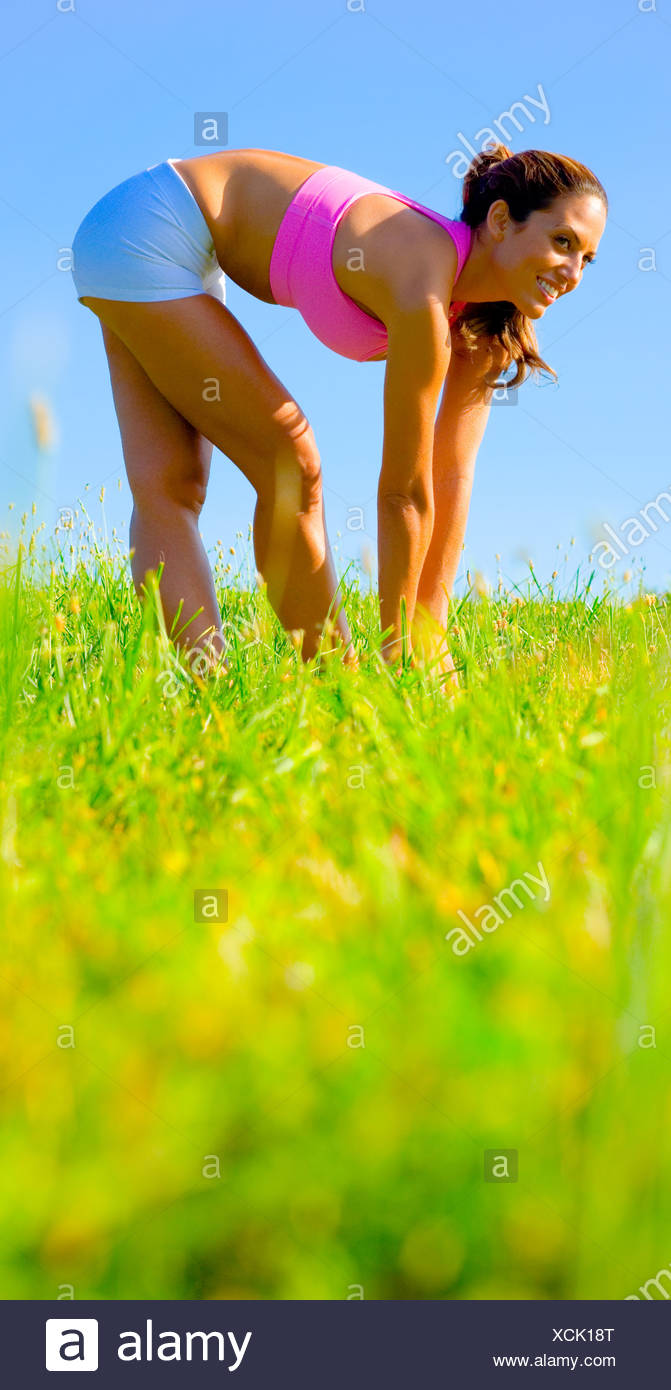Athletic woman working out in a meadow, from a complete series of photos. Stock Photo