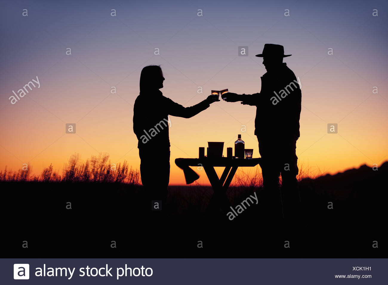 NamibRand Nature Reserve Namibia. Wolwedans sunset Silhouette two people couple - Stock Image