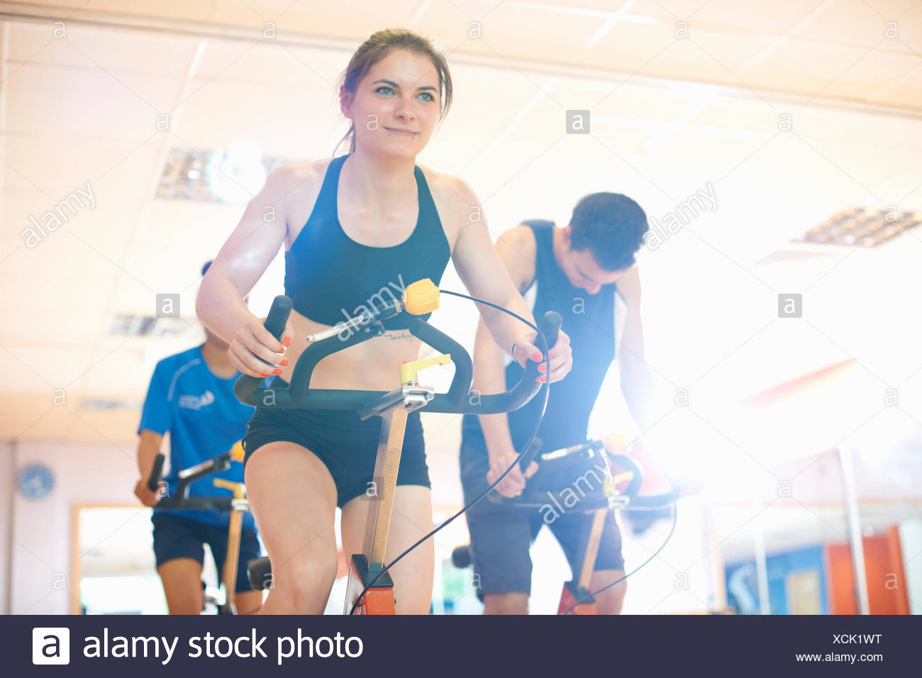 Young woman on exercise bike Stock Photo