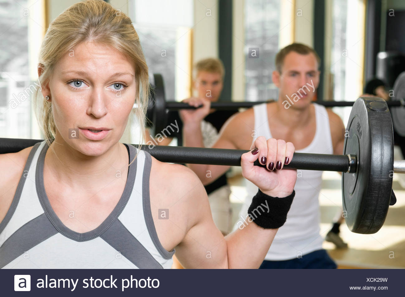 One girl and two guys working out - Stock Image