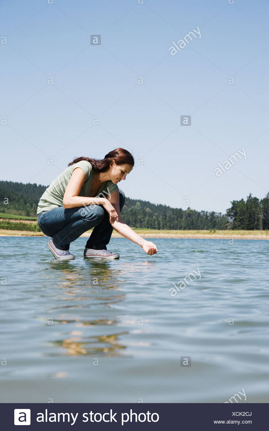 Woman standing on water dipping hand in - Stock Image