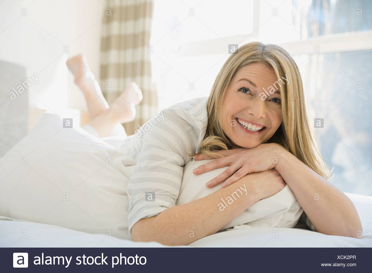 Smiling woman laying on bed - Stock Image